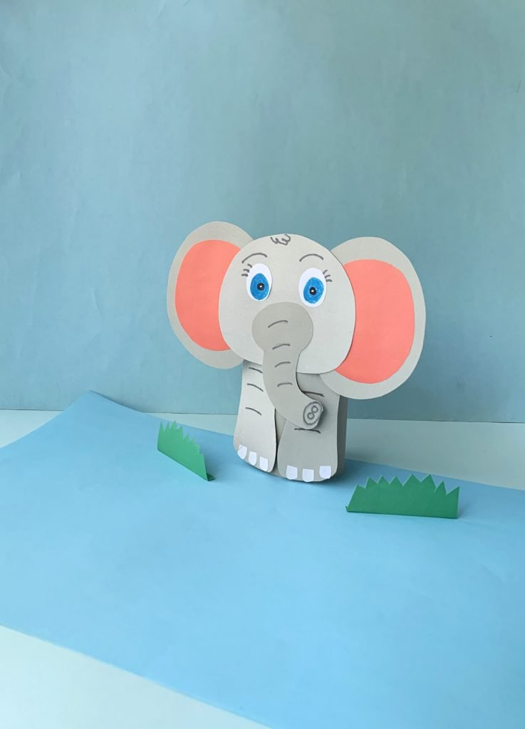 gray paper elephant made with an empty toilet paper roll with blue eyes and pink ears. the background is light blue