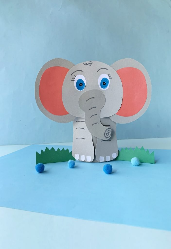 paper elephant with pink ears and blue eyes. paper grass on each side of the elephant with little blue poms in front