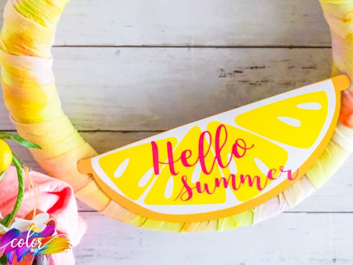 close up of yellow and peach colored Tie Dye Summer wreath hanging on a wall with hello summer on the front