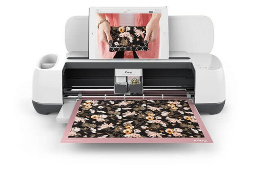 cricut maker with ipad in the holder and it is cutting floral fabric