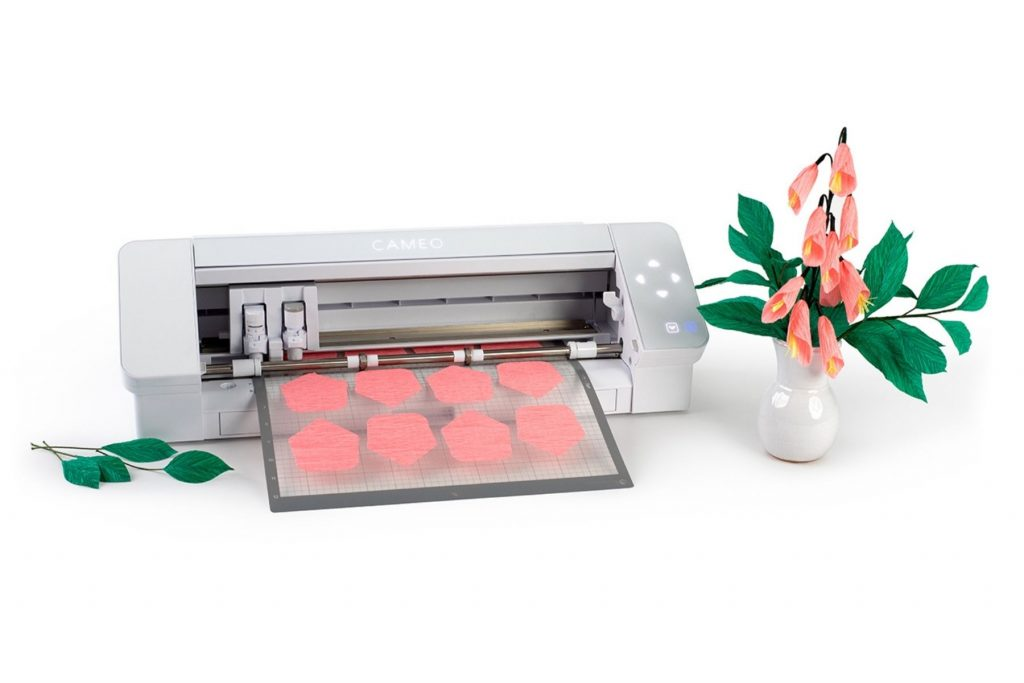 silhouette cameo cutting paper flowers with a vase of those flowers next to it, the flowers are peach