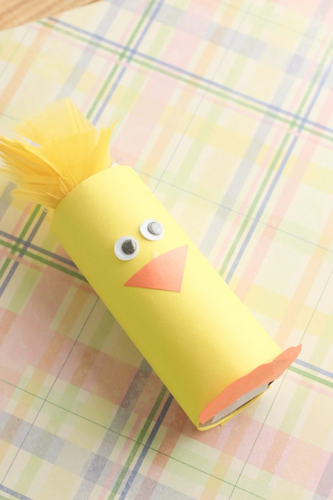 chick paper craft made from toiler paper roll with yellow feathers on the top, google eyes, and orange triangle beak; soft plaid background