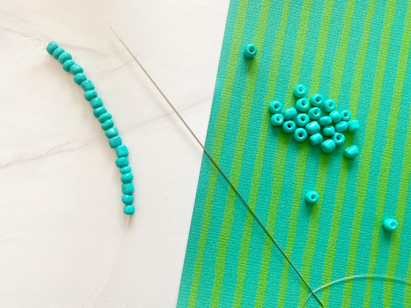 sliding blue beads onto string using bead needle