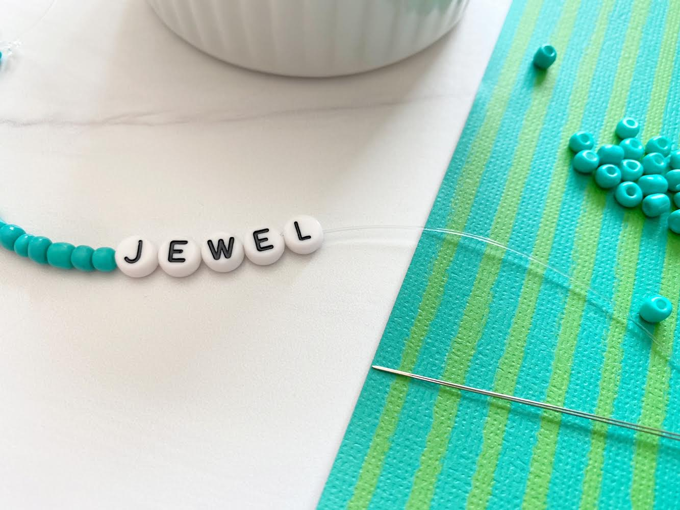 "finishing adding the beads onto the string; letters spell out ""jewel"""