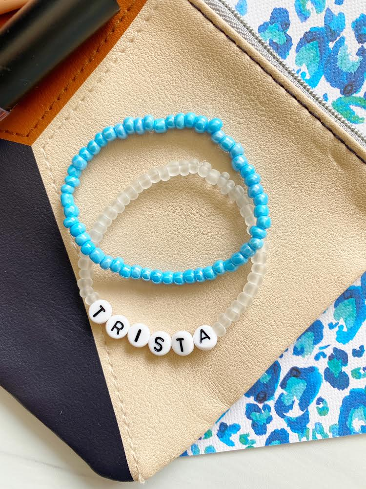 "two beaded bracelets; one with clear beads and letter beads in the middle that spells out ""trista""; the other is all blue"