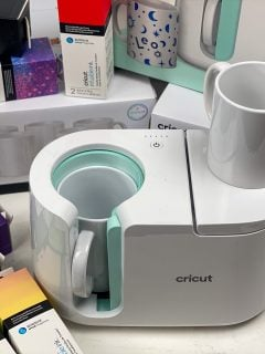 close up of cricut mug press with cricut infusible inks around it