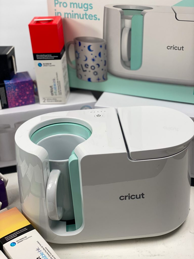 Cricut mug press with mug inside and Infusible Ink in the background