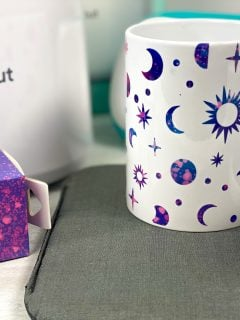 finished cricut mug with infusible ink, cricut joy and cricut mug galaxy mug with stars, sun and moons in pinks purples and blues. press in the background