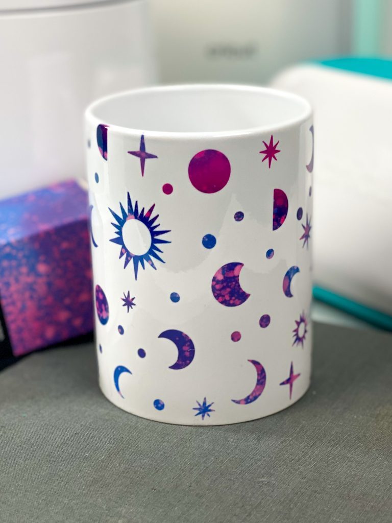 cricut infusible ink galxy mug with stars, sun and moons in pinks purples and blues.