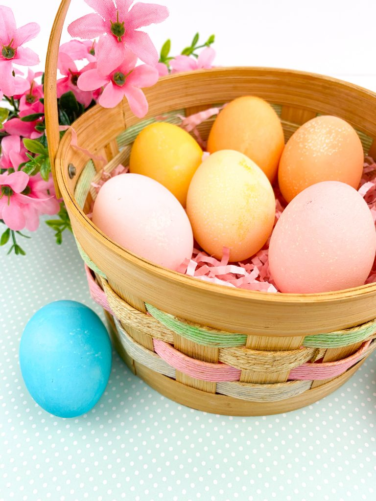 festive easter egg basket with colorful eggs dyed with kool-aid; colors: orange, pink, blue, yellow; flowers in background