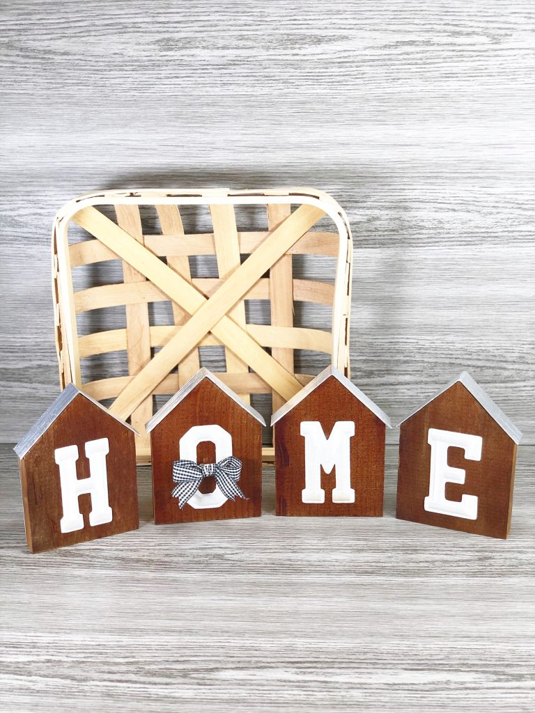 home sign made with dark wood and silver lining in front of tan basket