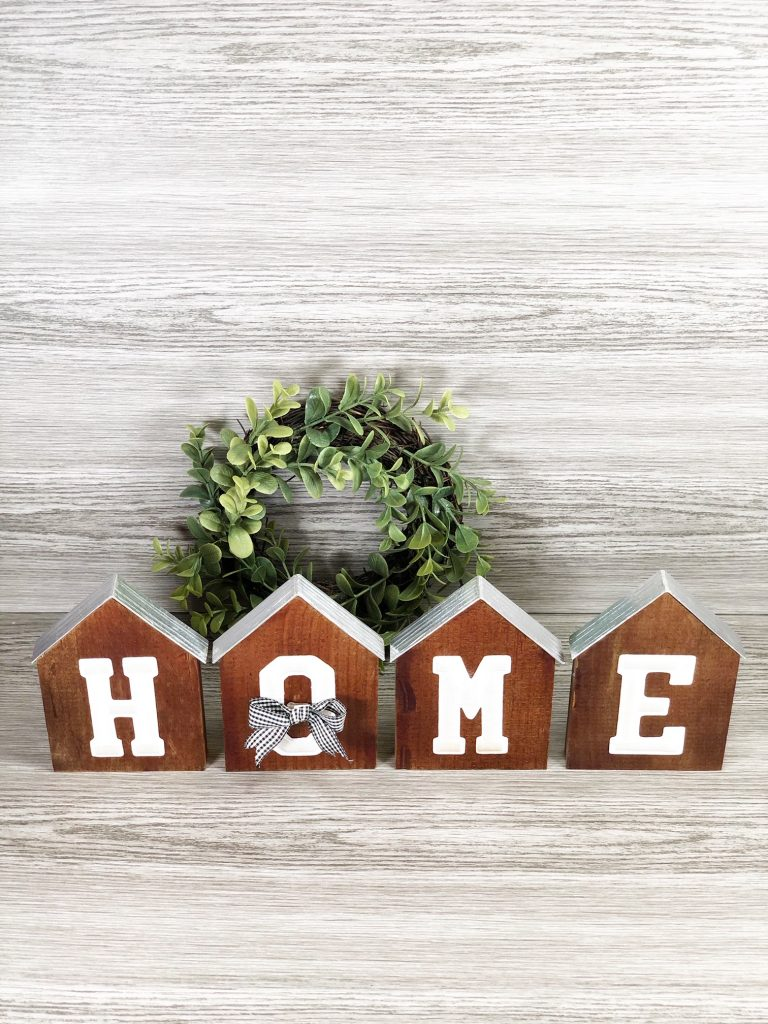 """home sign made form wood and dark spray paint with silver lining as the roof for each wooden piece, cute bow across the """"o"""" in front of circular greenery"""