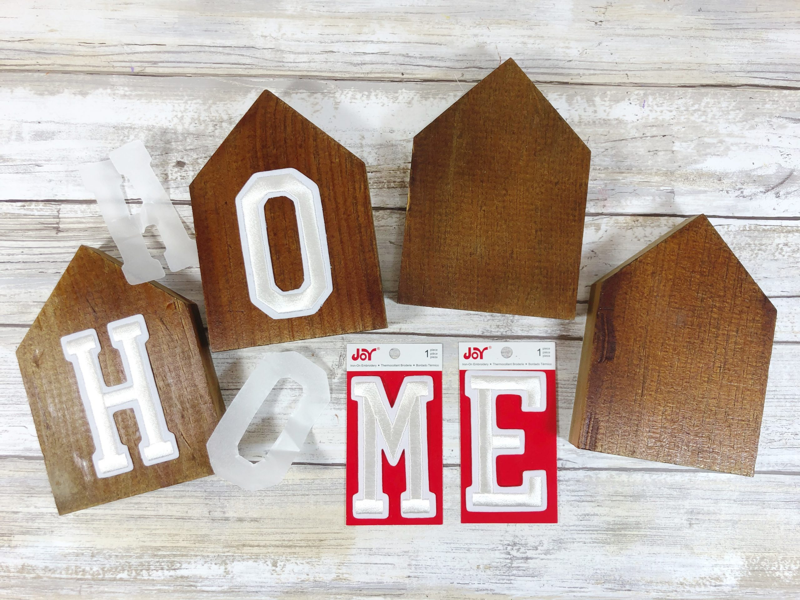 putting letters onto brown wood to spell out home