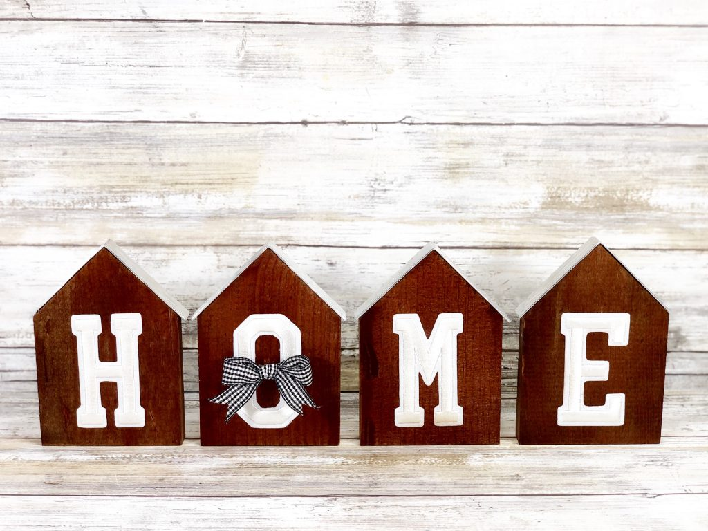 """home sign made form wood and dark spray paint with silver lining as the roof for each wooden piece, cute bow across the """"o"""""""