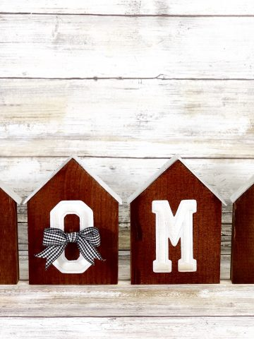 home sign made form wood and dark spray paint with silver lining as the roof for each wooden piece, cute bow across the