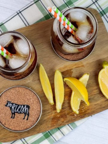 farmhouse coasters on wood serving plate with drinks that have lemons on the edge of the glass ans well as lemon wedges at the bottom