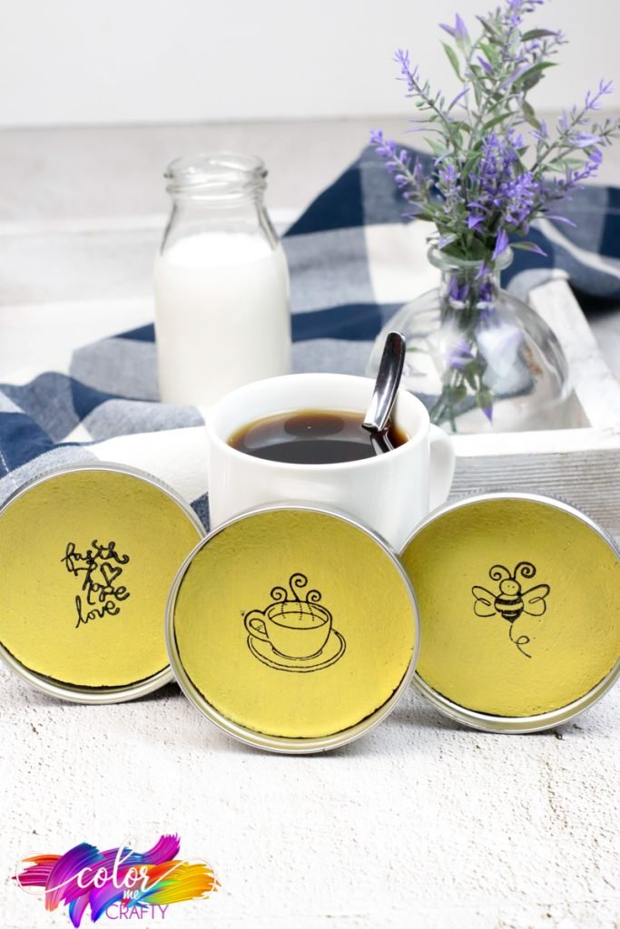 coasters made from cork and mason jar lids stamped with bumble bee, quotes, and coffee cup; coffee and milk sitting behind coasters; small purple plant in background