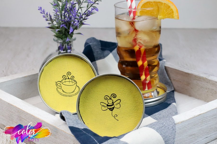 coasters made from cork and mason jar lids stamped with bumble bee and coffee cup; drink with straw sitting on top of one of the coasters; small purple plant in background