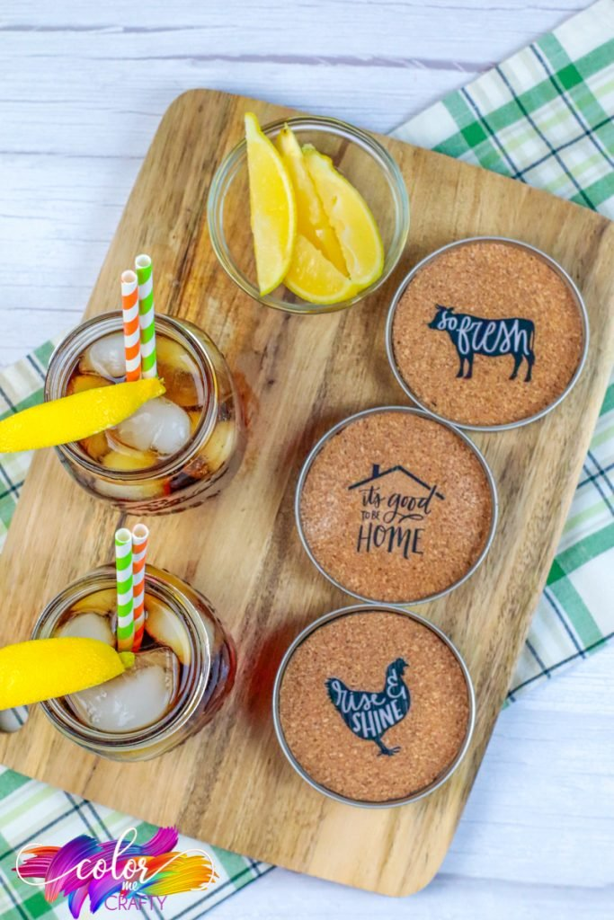 farmhouse coasters on wood serving plate with drinks that have lemons on the edge of the glass ans well as lemon wedges at the top vorner