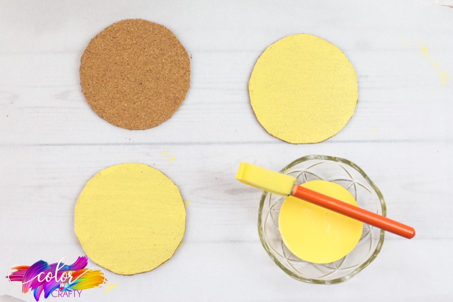one thick layer of yellow paint being applied to circular corks