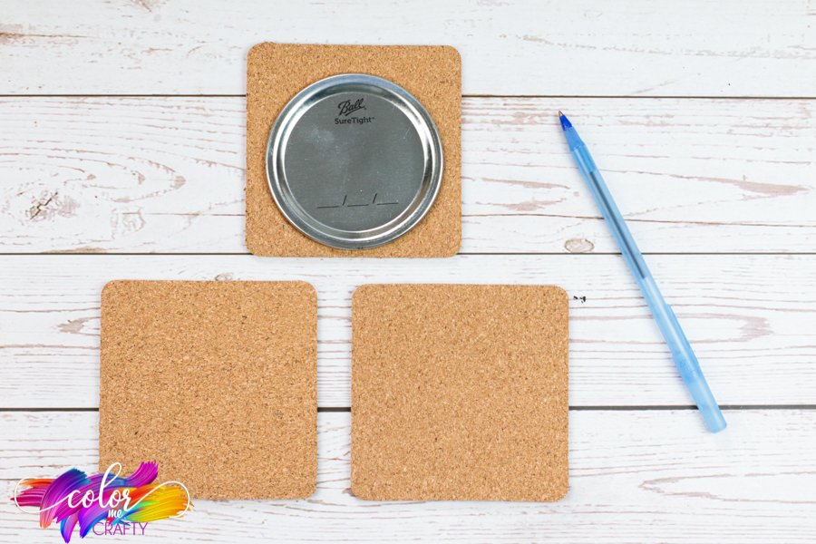 one mason jar lid on a square of cork with pen next to it preparing to trace