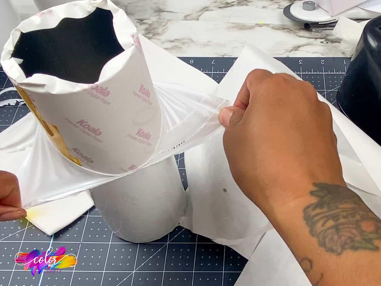 hands peeling shrinkwrap off skinny tumbler