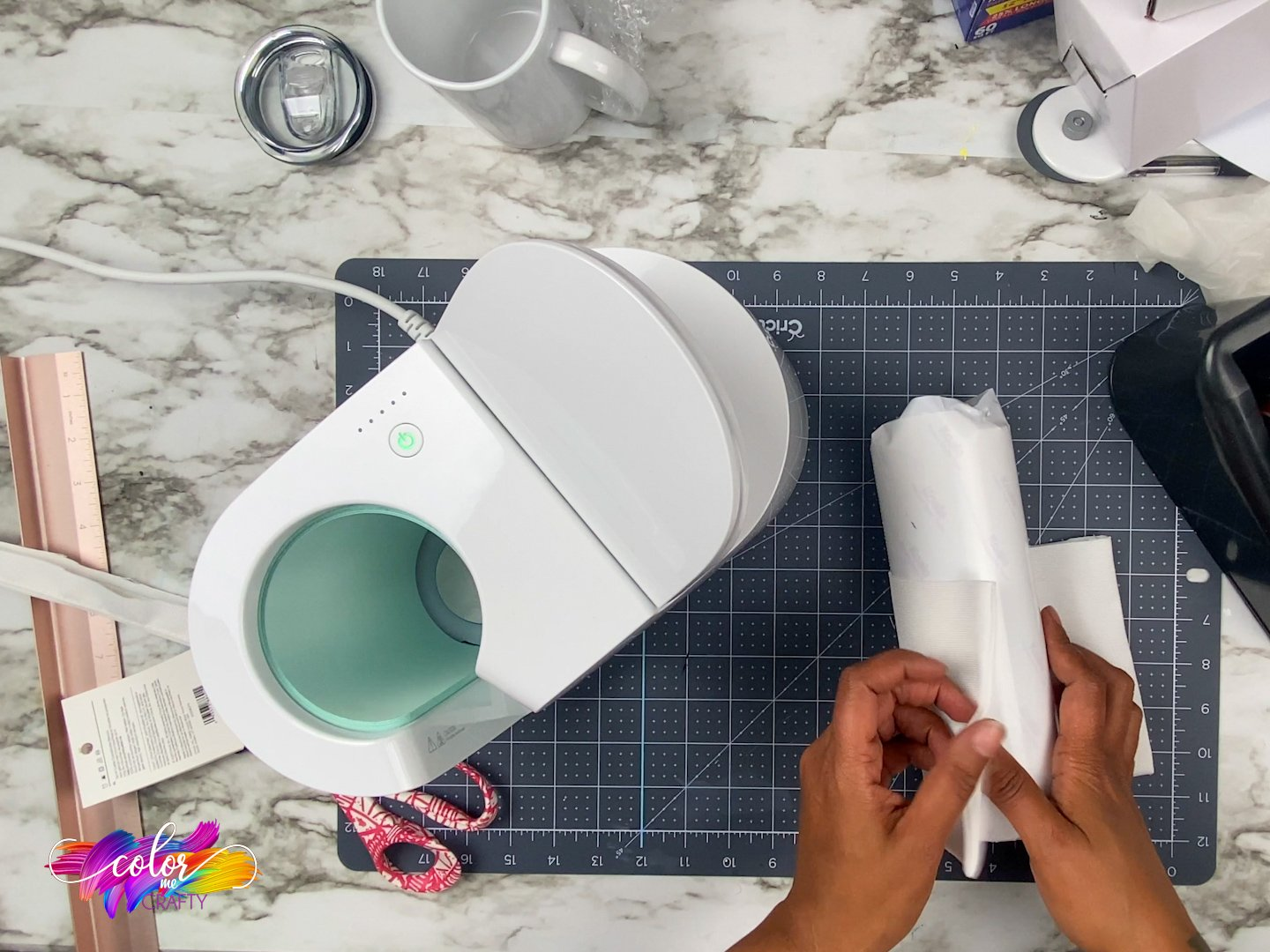 top view of the cricut mug press and next to it are hands working with a skinny tumbler
