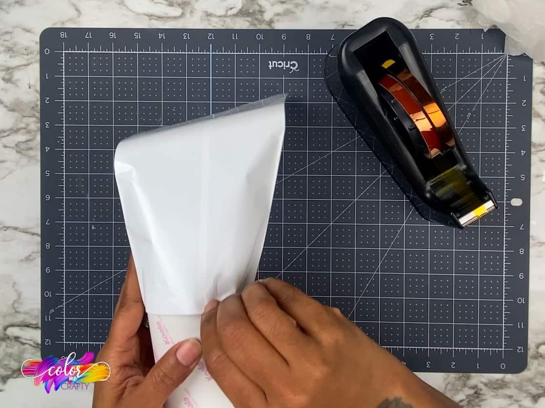 hand sliding a skinny tumbler in shrink wrap