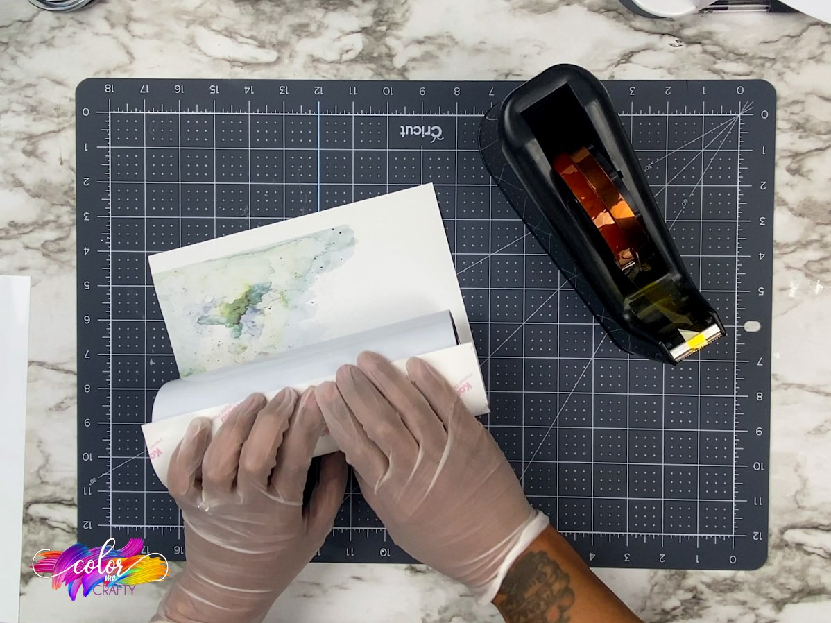 hands rolling a skinny tumbler in sublimation paper with heat tape next to it
