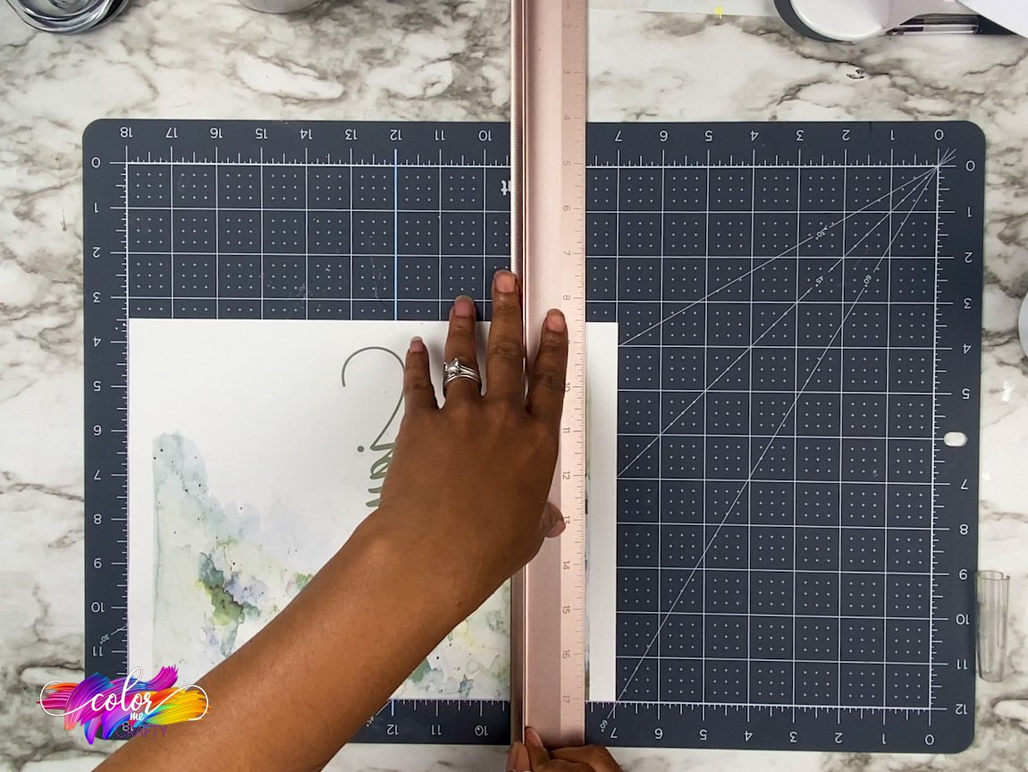 hands using a rose gold Cricut brand ruler on sublimation paper