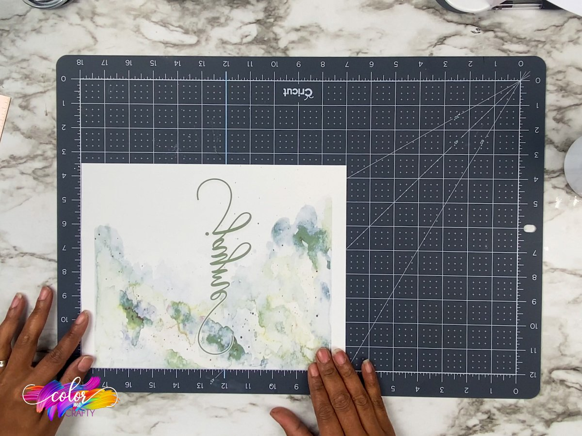 sublimation paper with a green design with a name sitting on top of a cricut self healing mat with hands in the image