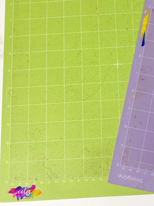 close up of standard grip cutting mat with dirt and debris on it