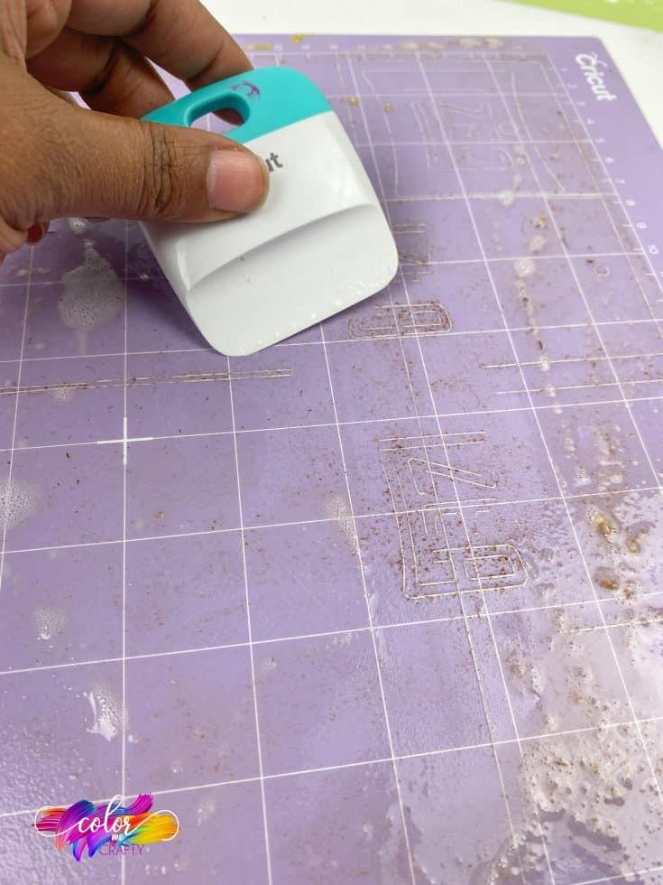cleaning a purple strong grip cricut cutting mat with a plastic scraper