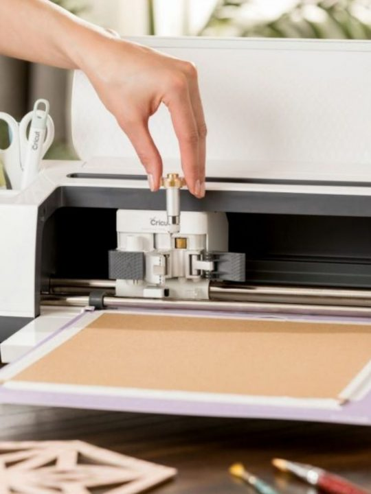 cricut maker machine with hand inserting a tool into the machine