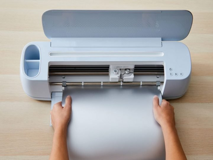 cricut maker 3 with a hand inserting smart vinyl into the machine