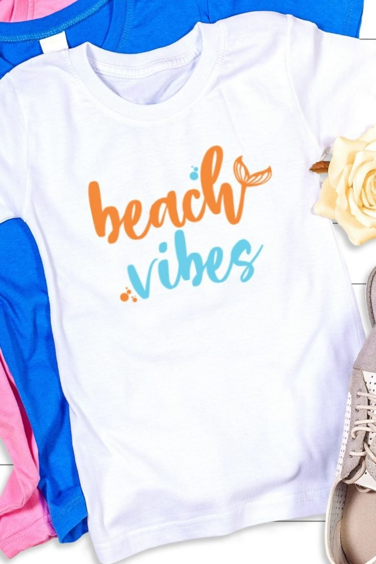 white shirt with a pink one and a blue one behind it that says beach vibes only