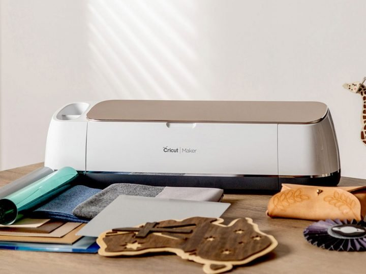 Cricut maker machine with materials and projects surrounding it