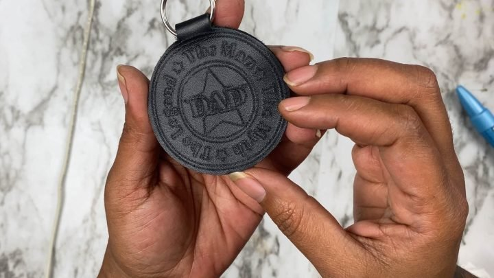cricut leather keychain being held by hands