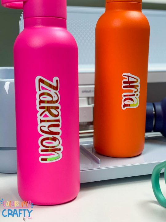 pink and orange water bottles with names on them in layered vinyl