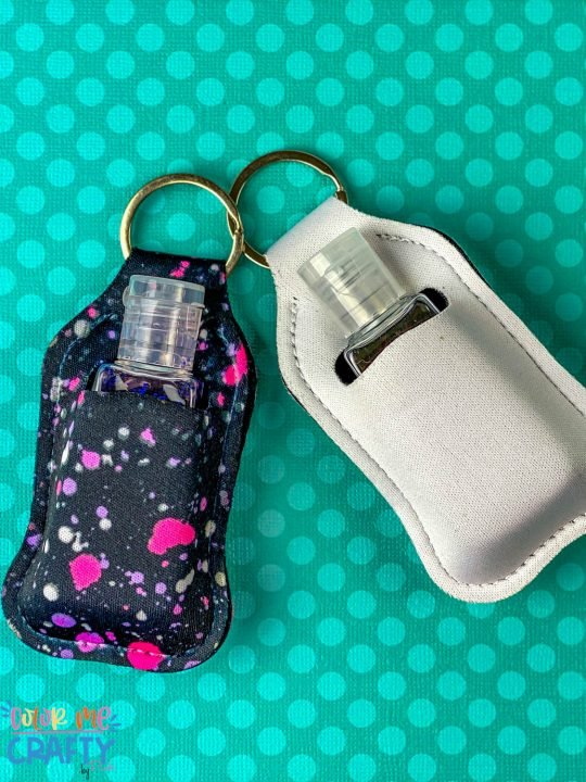 2 hand sanitizer pouches cricut infusible ink on a teal polkadot background