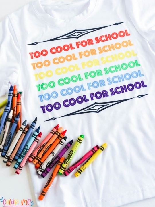 white sublimation t shirt that says too cool for school in the colors of the rainbow with crayons