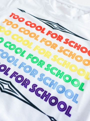 top view of white sublimation t shirt that says too cool for school with crayons