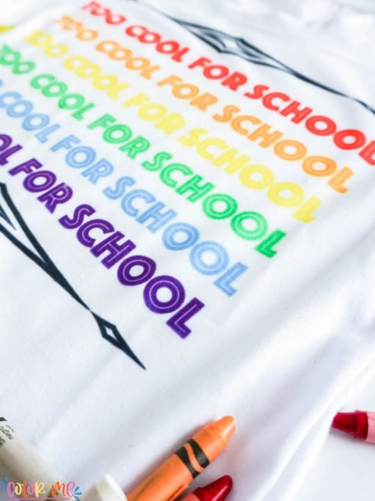 side view of white shirt that says too cool for school with crayons