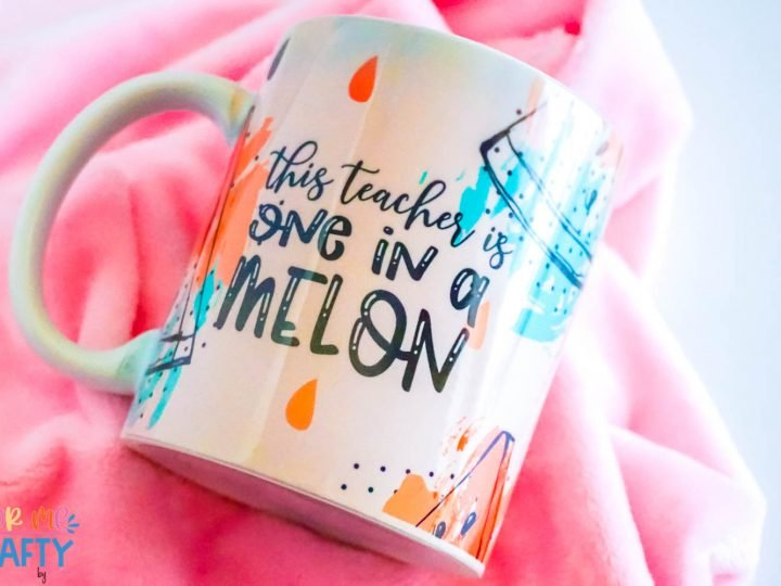 sublimation coffee mug that is laying flat and says one in a melon in pinks and teals with black words on a pink background