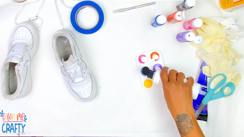 pouring textile medium into paint for shoes