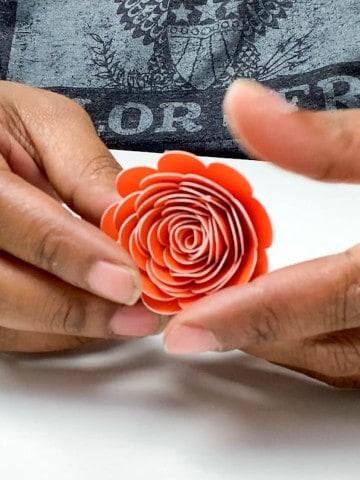 orange rolled paper rose in hands
