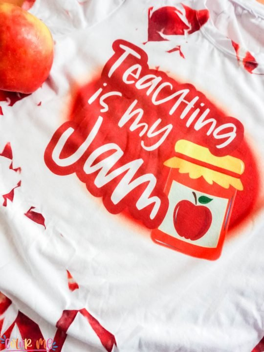 close up shirt in red with words teaching is my jam with apple in the shot on an orange background