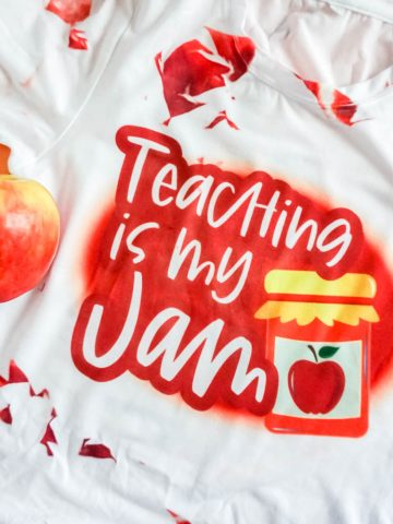 close up shirt in red with words teaching is my jam an with apple in the shot
