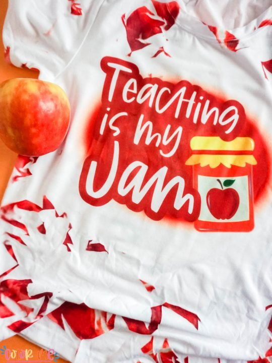 close up tie dye sublimation shirt in red with words teaching is my jam with apple in the shot on an orange background