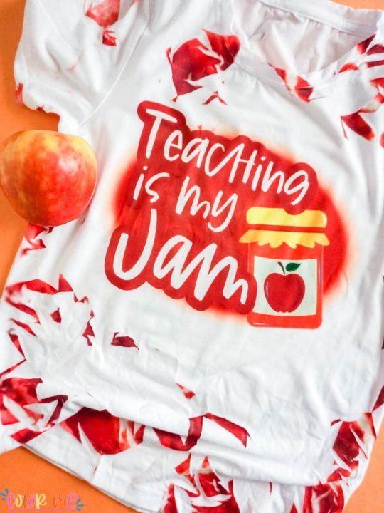 tie dye sublimation shirt in red with words teaching is my jam with apple in the shot on an orange background